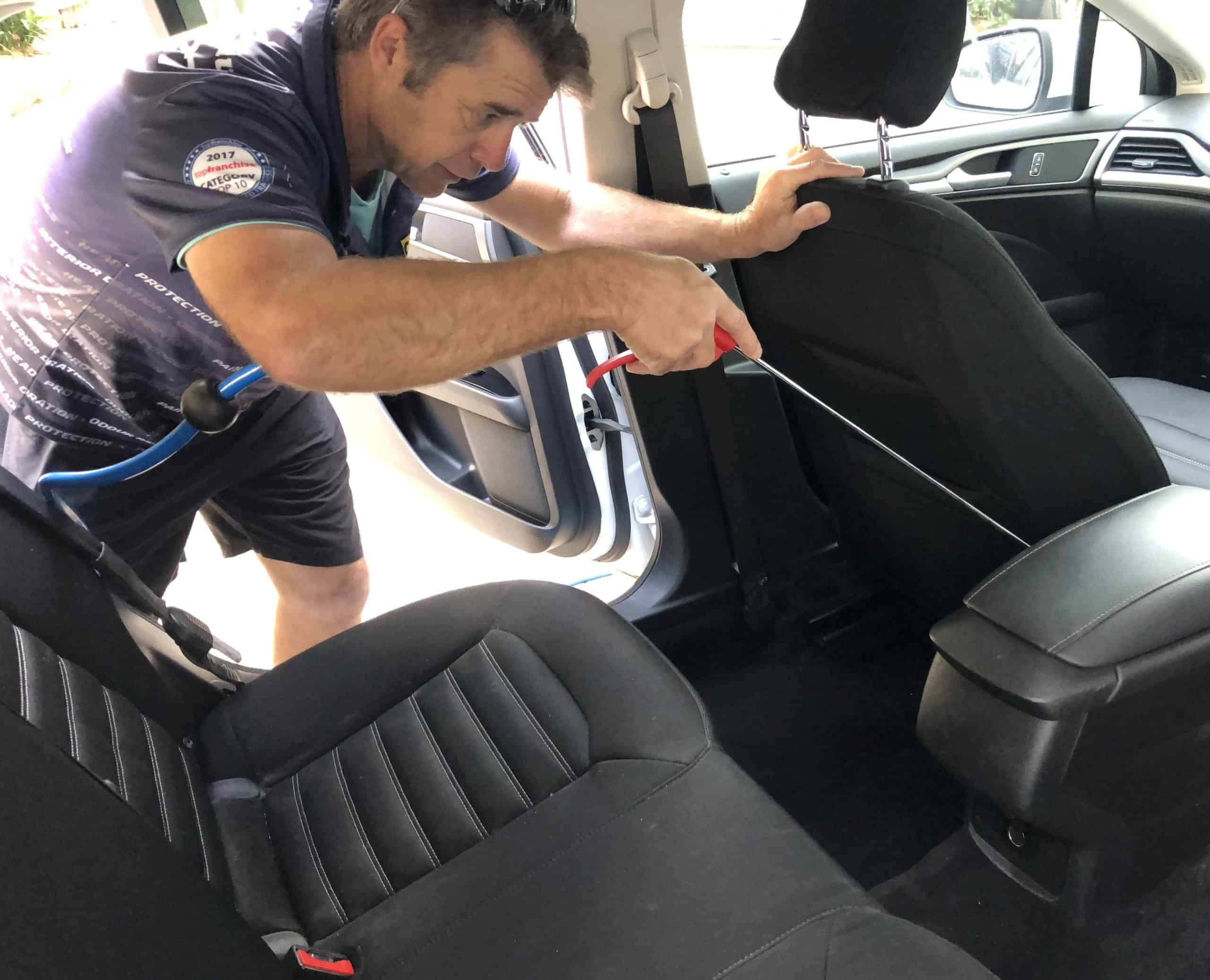 cleaning in between car seats with an air gun to get into every nook and cranny