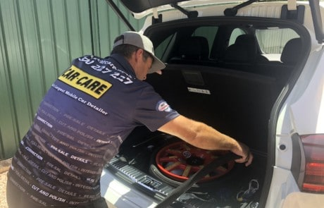 A car detailer performing an interior detail clean on the boot of a car using a vaccum cleaner to clean by the spare wheel