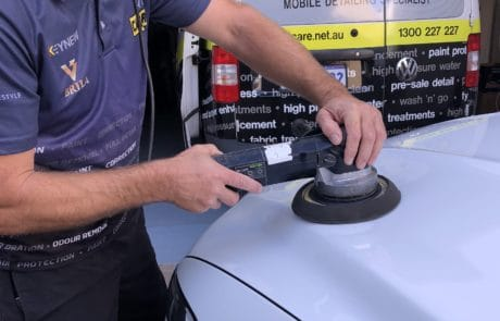 Using machine buffer to apply polish to white car