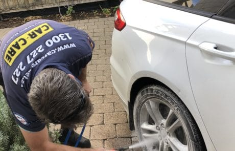Applying wheel cleaner with a Soda Blaster to white Ford alloy wheels